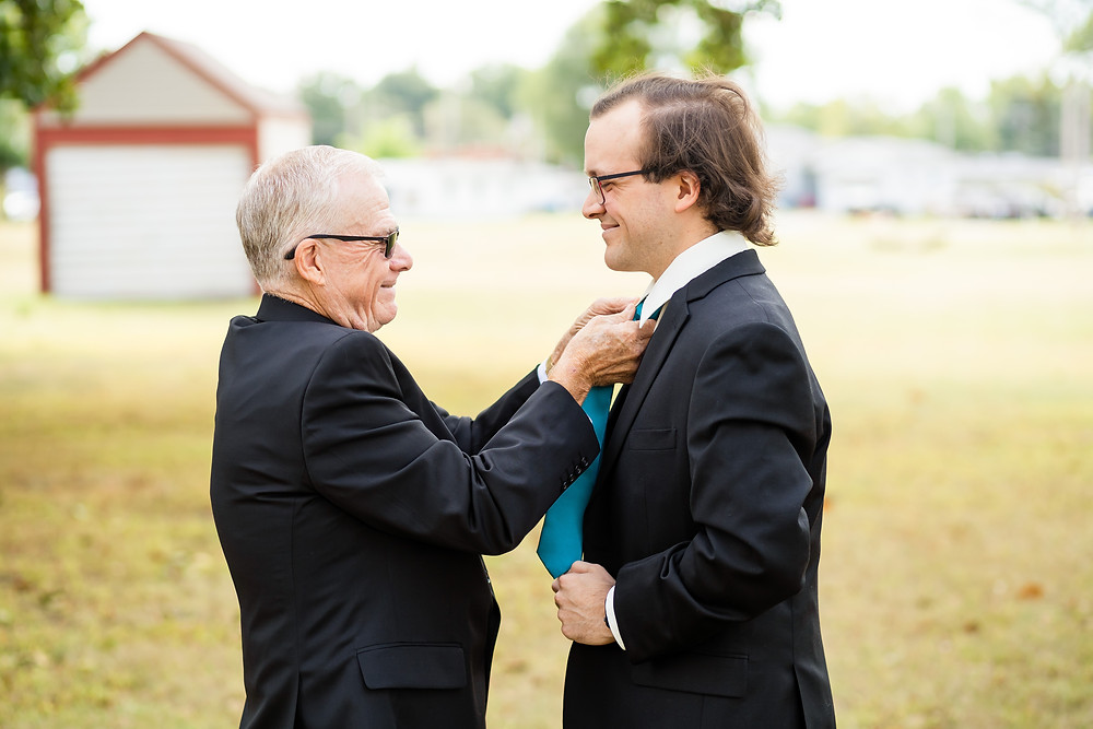 Father and son smiling at each other while father ties tie