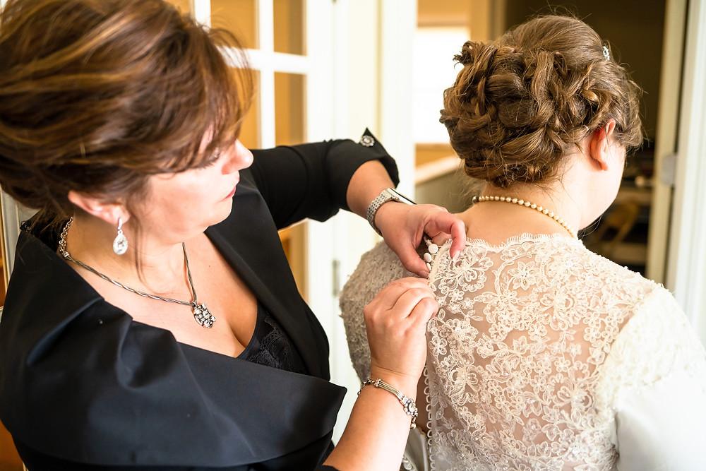 Mother helping bride button wedding dress