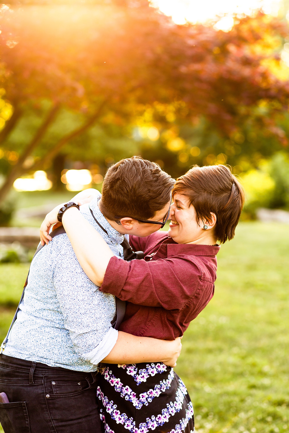 Couple with arms wrapped around each other and leaning in for a kiss, but laughing instead