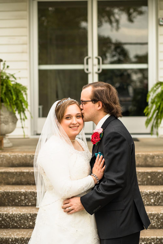 Groom kissing brides temple