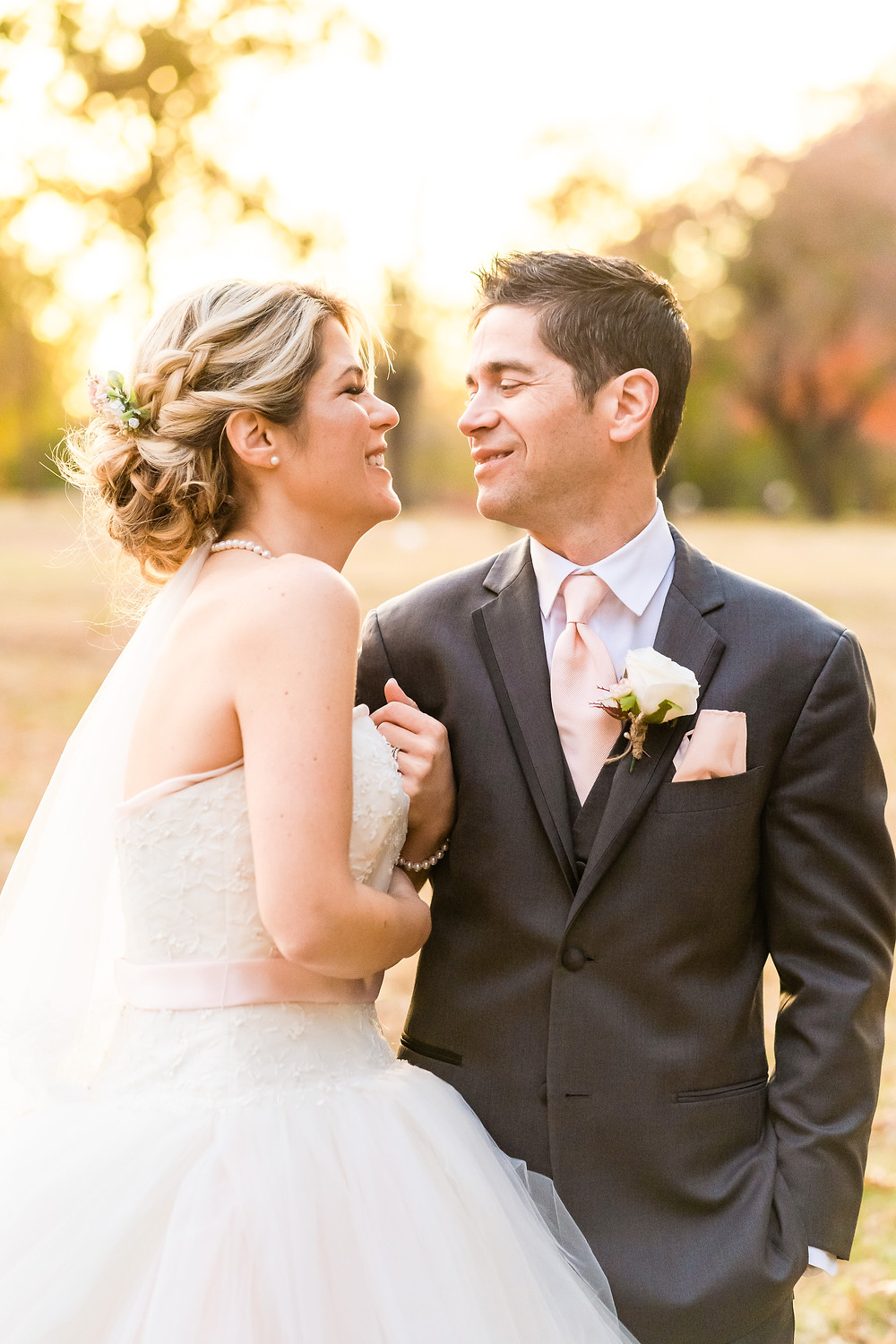 Bride and groom smile at each other in the sunset