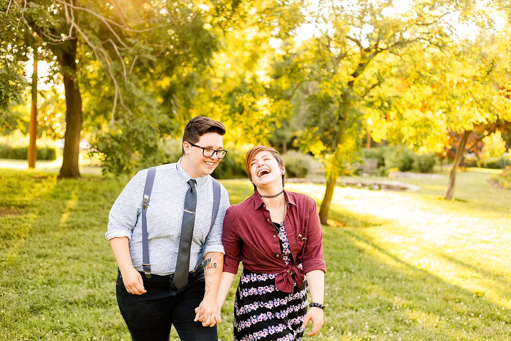 Couple holding hands and laughing while walking towards the photographer