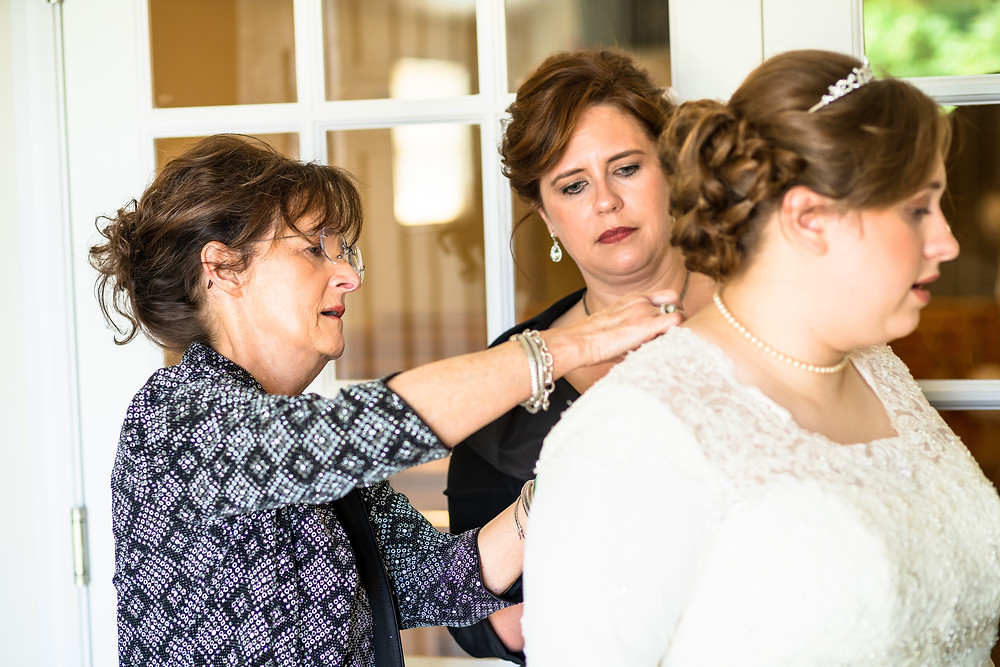Mother and grandmother of the bride helping her button wedding dress