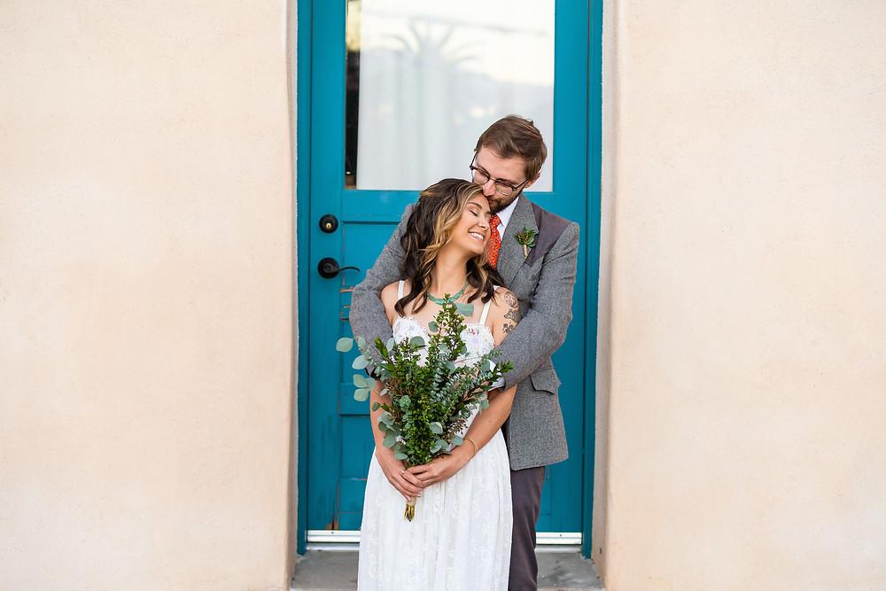 Bride and groom hugging in front of a teal door