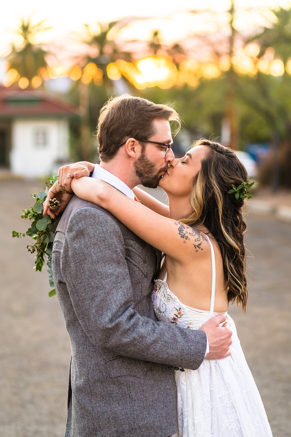 bride and groom kissing in front of sunset