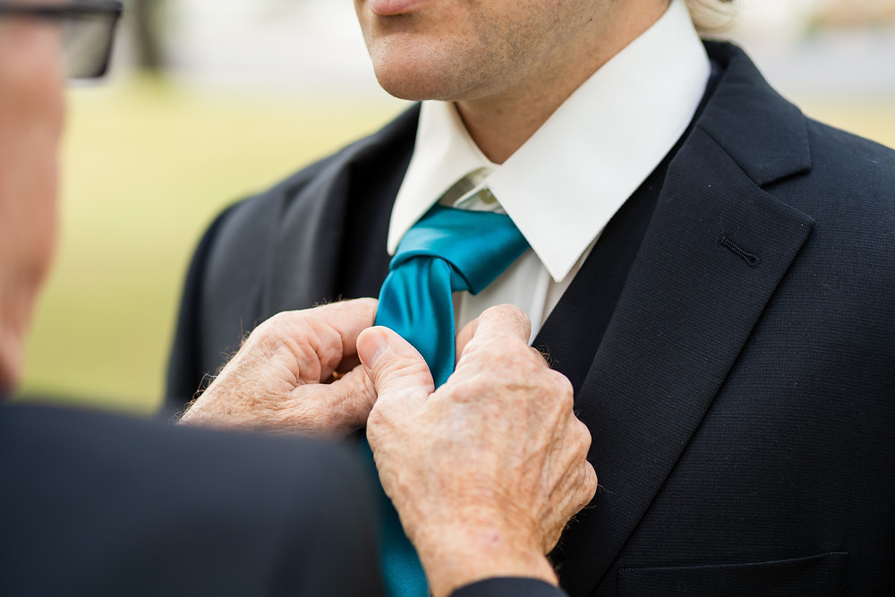 Father helping son tie his tie on his wedding day