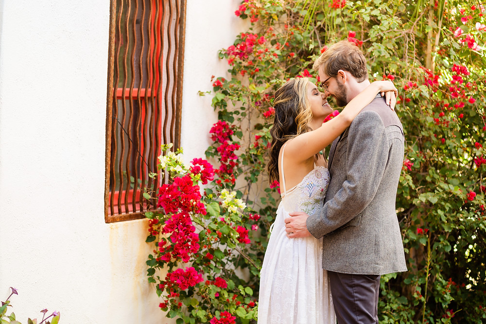 bride and groom touching noses in front of flowers