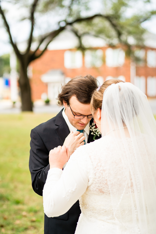 Bride helping groom adjust his jacket