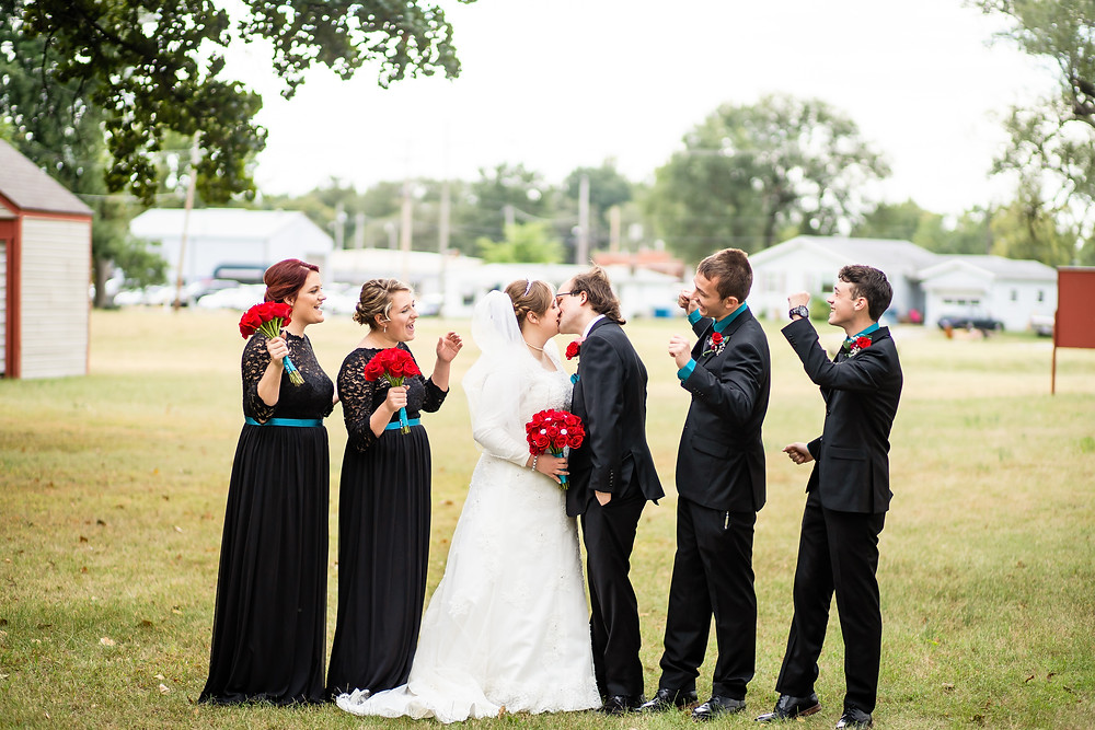 Bride and groom kiss while wedding party cheers