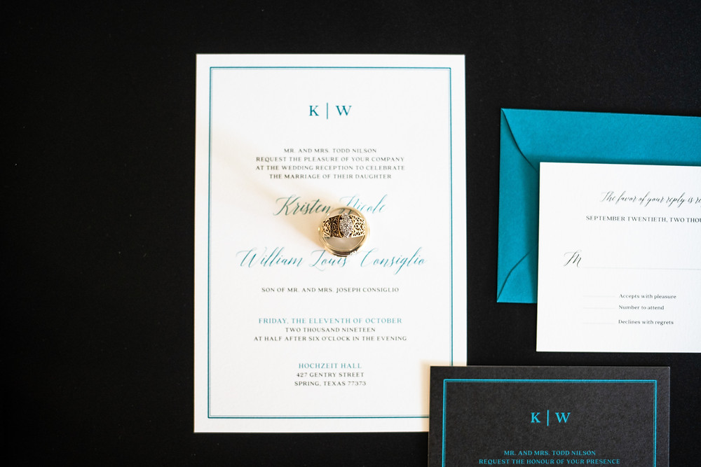 Wedding rings on top of a wedding invitation suite