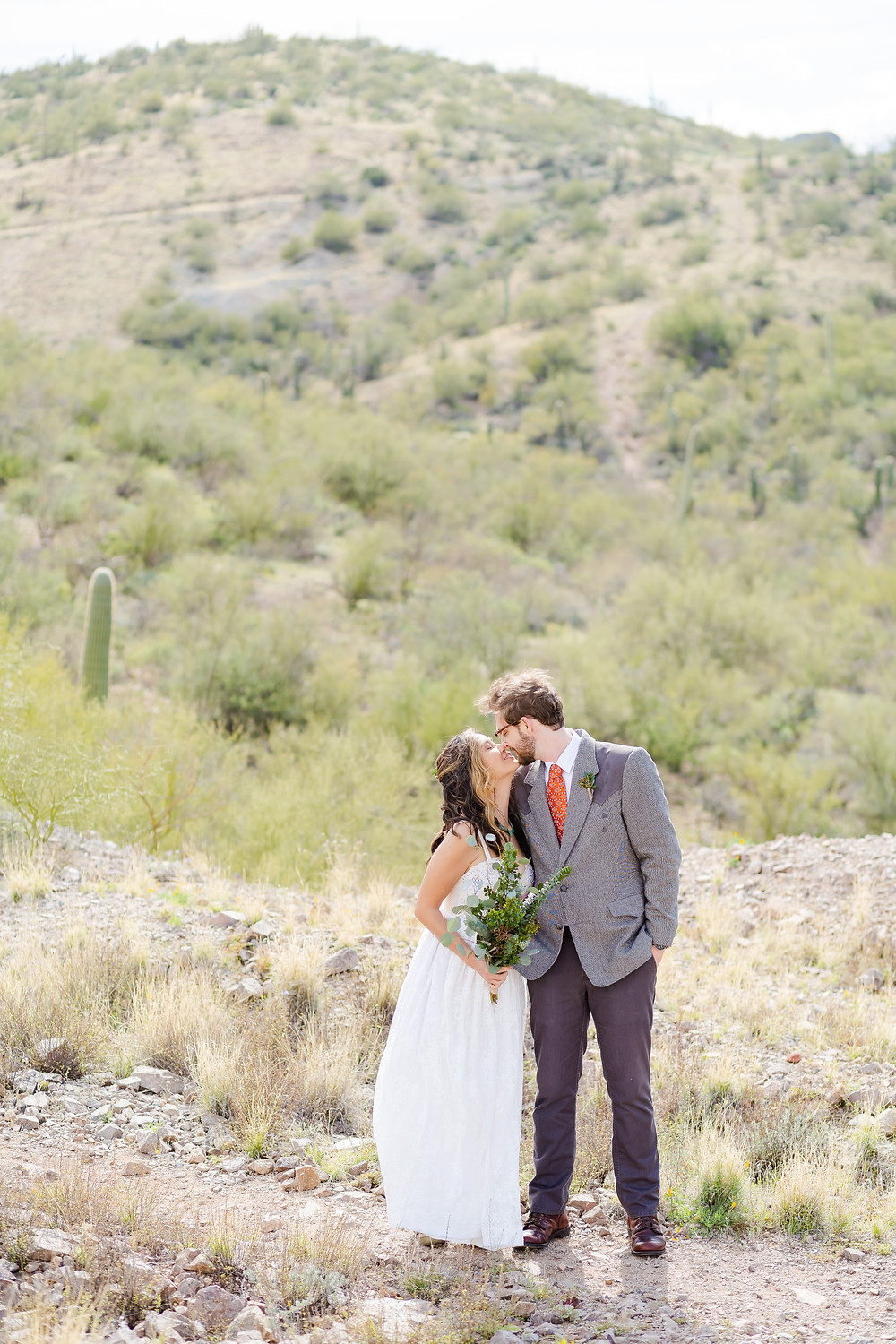 bride and groom touching noses in tucson dessert