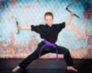 Portrai of a karate boy holding two knifes