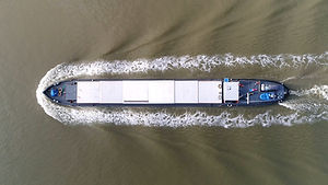 Aerial photo of barge moving over canal