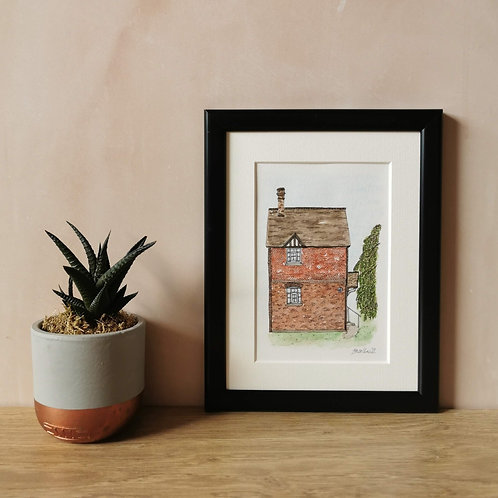 Jessica Sian Illustration, A5 Watercolour House Portrait in a black frame with white mount. Sat on a wooden table.