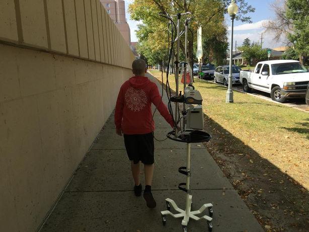 peditric cancer patient walking down sidewalk