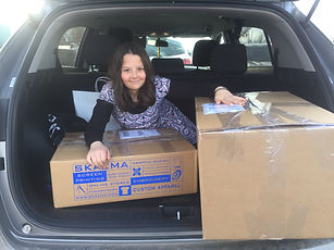girl in back of car with box shipments