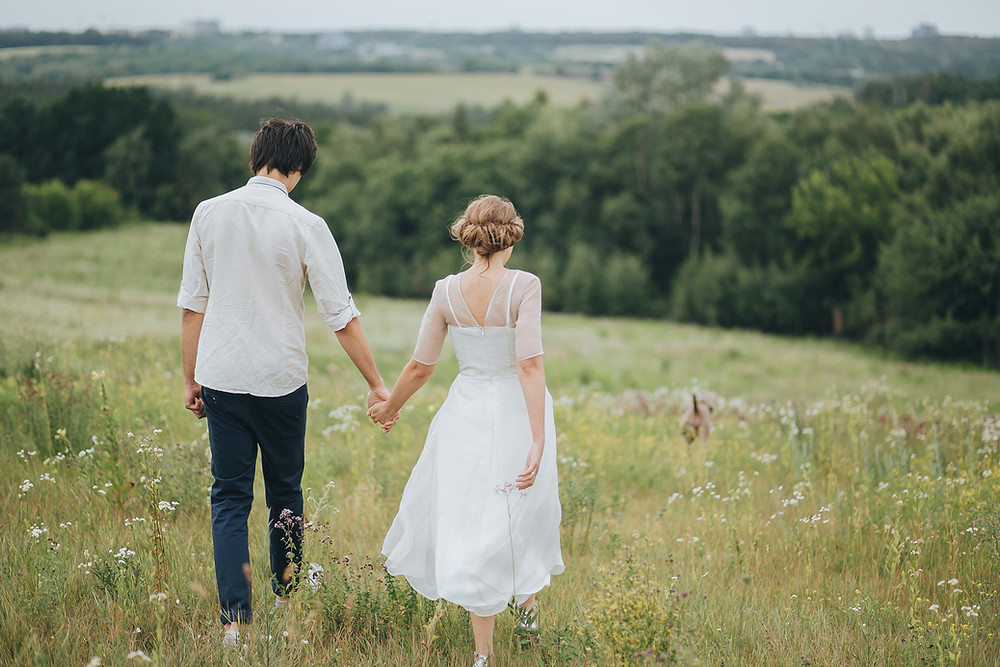Couple walking in a meadow after a celebrant wedding