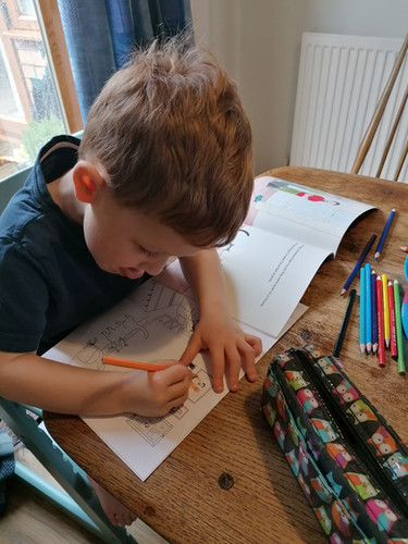 A young artist colours in his Colouring Book.