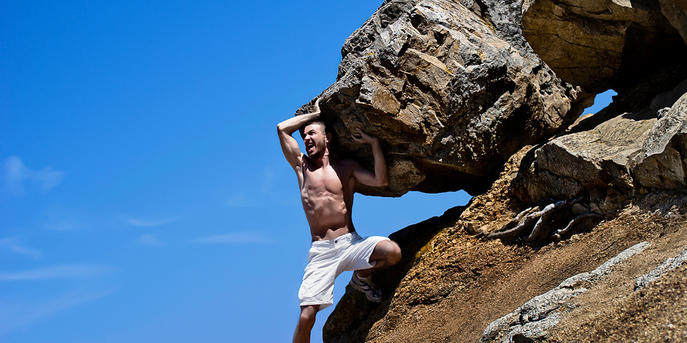 Guy holding back a boulder on a hill