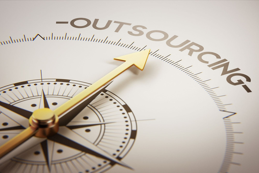 a compass that points to the word outsourcing