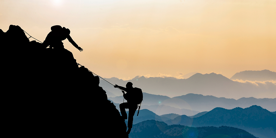 A business coach reaching out to help a business owner climb a mountain top