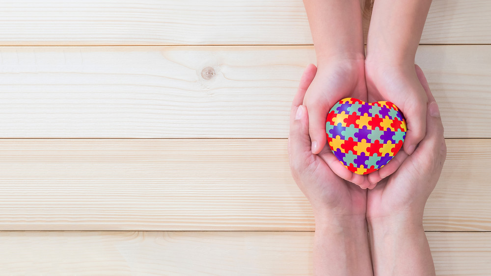 Two hands holding a heart made of the Autism symbol