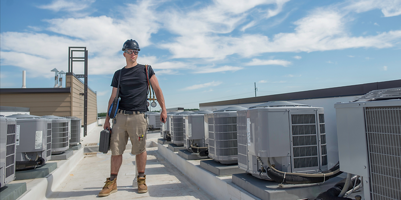 Air conditioner technician standing on the roof fixing an HVAC
