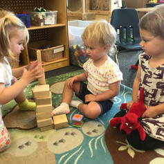 Three children building with blocks together