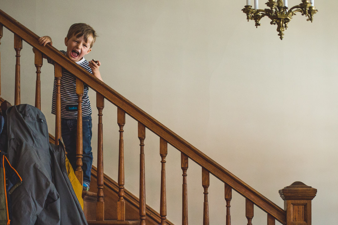 Boy leaning over a staircase pouting and yelling at camera