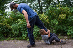 Child clings onto dad's leg as dad walks
