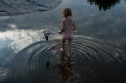 Child walks in water with net