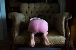 child hides in Antique chair