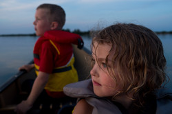 Siblings watch sunset from canoe during blue hour