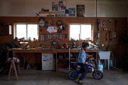 Boy rides bike in work shop