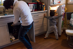 Dad uses garbage can while toddler looks in fridge