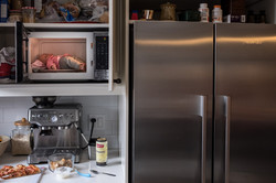 Baby doll in kitchen microwave