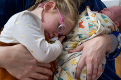 Mother's arms holding swaddled newborn baby and upset toddler