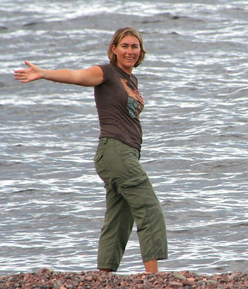 Vicki standing infront of water on a rocky shoreline smiling with her arms outstretched.