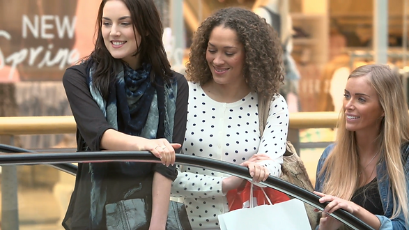 three-female-friends-riding-escalator-sh