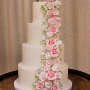 Fondant covered cake with cascade of handmade sugar roses and flowers