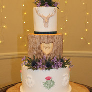 Rustic Scottish theme with thistles, wood effect tier and relief stag head motif