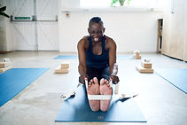 Yinka laughing in a seated forward bend yoga pose.