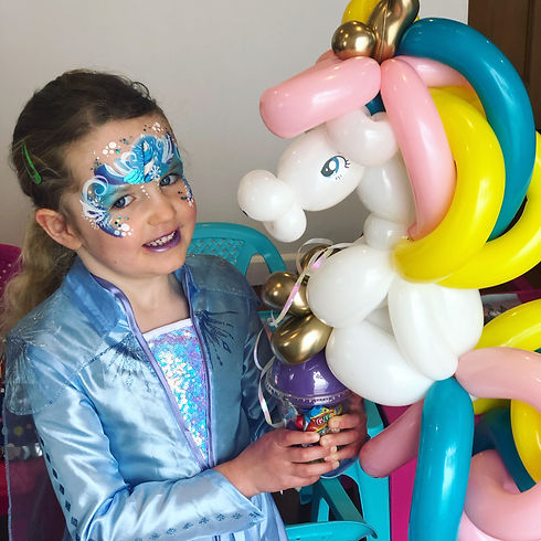 Girl with frozen face painting holding a large unicorn balloon animal Wellington New Zealand