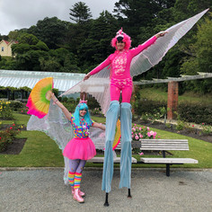 Flamingo stilt walker and unicorn circus performer