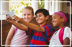 Portrait of happy little school kids taking selfie in school corridor_edited