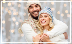 winter, fashion, couple, christmas and people concept - smiling man and woman in hats and scarf hugg