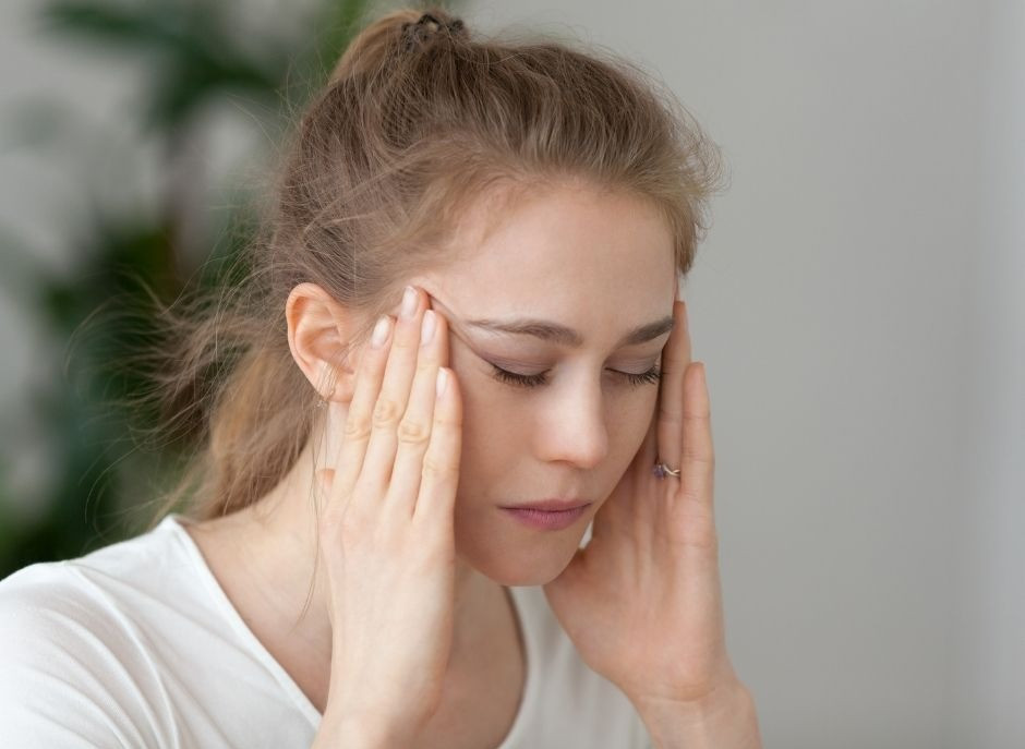 A woman with her hands on her temples, eyes closed & looking fatigued.