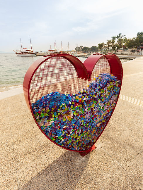 heart-shaped-container-on-the-waterfront-filled-with-multi-colored-plastic-bottle-caps.jpg