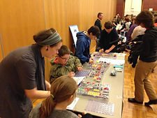 Adults and young people look at circuit board kids on a table