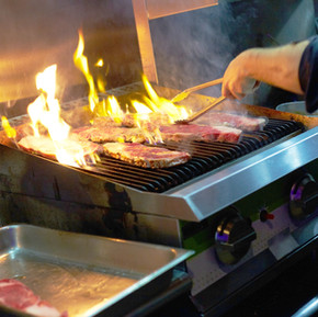 Cropped image of chef grilling steaks in